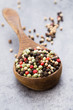 Quadro Peppercorn mix in a wooden bowl on grey table.