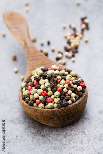 Peppercorn mix in a wooden bowl on grey table. - 235731283