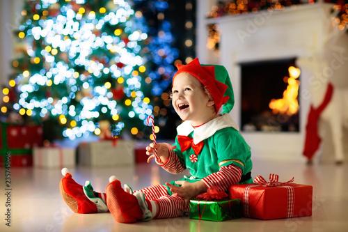 Kids at Christmas tree. Children open presents - 235745096