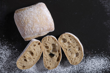Loaf of ciabatta bread and sliced on a black background