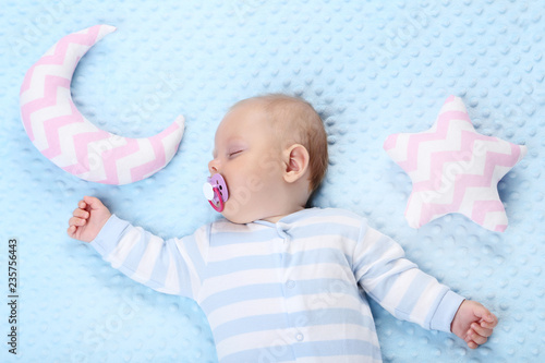 Baby boy with soft toys sleeping in blue bed - 235756443