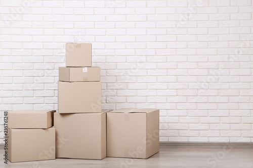 Leinwandbild Motiv Cardboard boxes on brick wall background