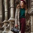 Leinwanddruck Bild - Outdoor fashion portrait of woman wearing trendy animal, leopard print faux fur coat, beret, sweater, corduroy trousers, holding  reptile skin textured bag, posing in street of city. Copy, empty space