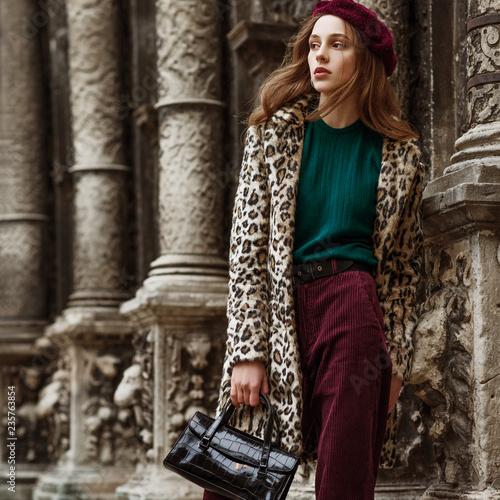 Leinwandbild Motiv Outdoor fashion portrait of woman wearing trendy animal, leopard print faux fur coat, beret, sweater, corduroy trousers, holding  reptile skin textured bag, posing in street of city. Copy, empty space