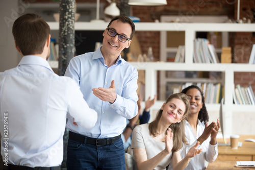 Middle aged happy smiling boss, mentor congratulating employee, praise for good work, new project, idea for startup, shaking hand, welcoming new member of business team, colleagues applauding