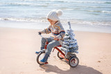 Santa claus kid in Christmas sweater. Happy child on the bicycle or tricycle near water. Xmas party celebration, childhood. Winter holiday vacation. New year small boy at sea beach.
