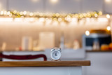 little alarm clock on a table with Christmas lights on background. Kitchen interior - 235772278