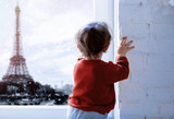 Little baby boy stay near window and looking on Eiffel tower in snow time on background.