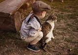 Cute little boy enjoying an autumn warm day with a cat - 235785899