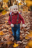 Cute twins looking at falling down autumnal leaves - 235786421
