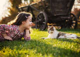 Cute little girl smiling to a cat - 235788600