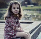 Portrait of a miserable little girl sitting on a jetty - 235788689