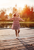 Cheerful, littlel girl realxing on a jetty - 235789063