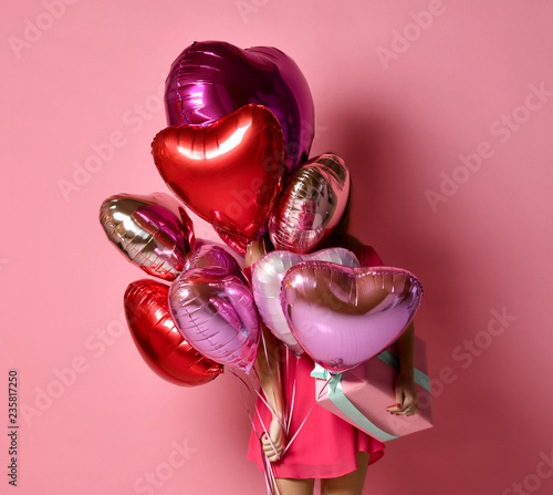Girl with colorful hearts air balloons hiding behind on birthday holiday party having fun and celebrating with gift  - 235817250