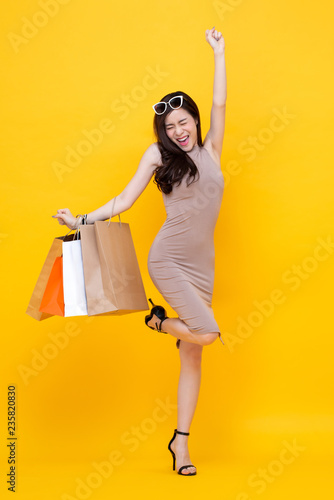 Leinwandbild Motiv Happy excited Asian woman with shopping bags for sale concept