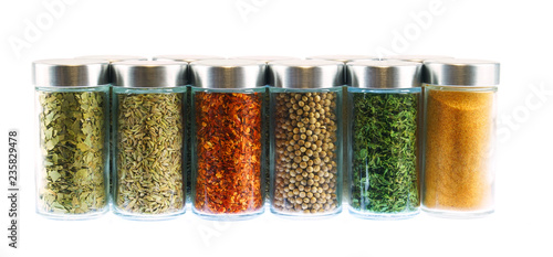 collection of spice and herbs seasoning in glasses bottles isolated on white background