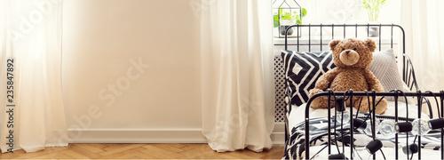 Pluszowa zabawka na łóżku dziecka w minimalne czarno-białe wnętrze sypialni z miejsca na kopię. Prawdziwe zdjęcie