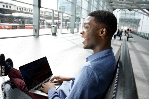 Leinwandbild Motiv Side of african american businessman waiting at station with laptop
