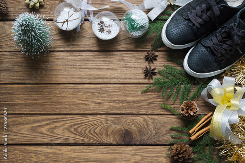 Leinwanddruck Bild Flat lay black sneaker, mini christmas tree, gold and silver bows, Christmas ornaments on wood background, Merry Christmas fashion background concept. Top view with copy space.