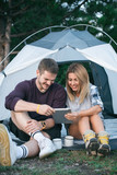 Smiling young couple using tablet computer on a camping
