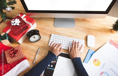 Businesswoman working in christmas holiday at the office with christmas decoration on table.