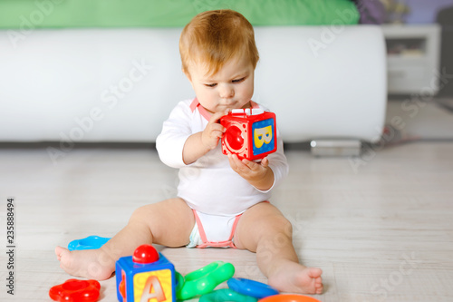 Adorable baby girl playing with educational toys in nursery. Happy healthy child having fun with colorful different toys at home. Kid trying to build plastic pyramid and using blocks with letters