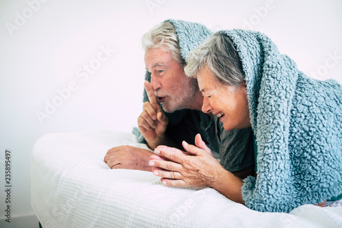 Leinwanddruck Bild Happy adult couple have fun laughing together at home in the nedroom under the sheet in the wake up morning time - together forever with happiness concept for caucasian people in love