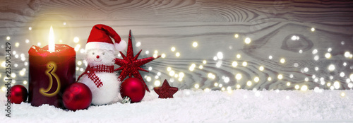 Christmas background with third Advent candle and Snowman with red decoration. - 235903429