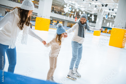 Leinwanddruck Bild happy family in hats and sweaters holding hands while skating together on ice rink