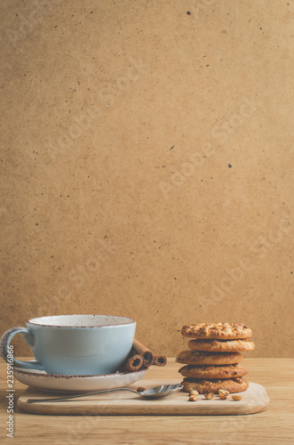 cinnamon sticks, cookies and a cup of coffee/cinnamon sticks, cookies and a cup of coffee on a wooden background with copy space - 235916866