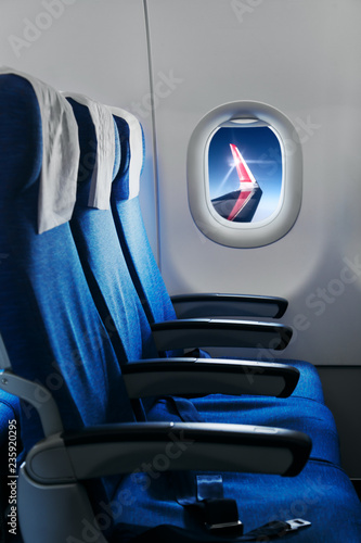 Empty air plane seats. Blue sky and the wing in the window. Airplane interior