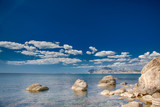 seascape with crystal clear turquoise shallow water on coast of sea with different size stones on beach at sunny day and some clouds on horizon