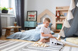 Cute little boy playing with wooden blocks in stylish bedroom with scandinavian design, real photo