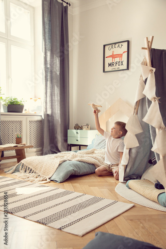 Little boy playing with toy airplane in scandinavian kid playroom with tent