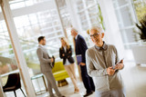 Portrait of senior businesswoman with digital tablet while other business people standing in background - 235939024