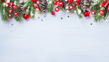 Christmas background with snowy fir branches, cones and bokeh lights. Holiday banner or card.