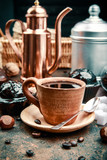 Crafting coffee in clay cup with bean cezve and chocolate cake