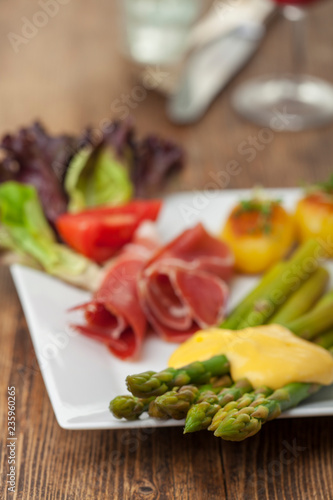 zielone szparagi z sosem holenderskim na talerzu