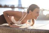 Girl doing push ups in the street, along the riverside,