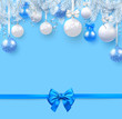 Blue Christmas and New Year background with fir branches, Christmas balls and satin bow.
