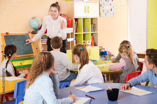 Teacher standing at blackboard in classroom