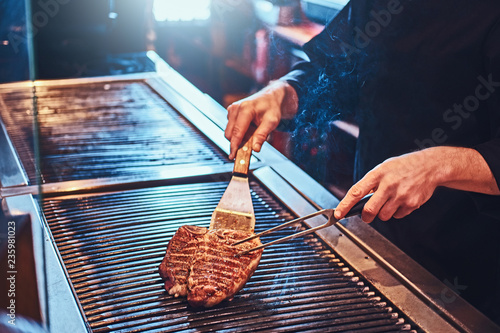 Foto Murales Cropped photo of a chef cooking delicious beef steak