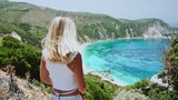 Joy and happiness concept, young blonde woman shaking her hair, hairs flying in the wind. She enjoying amazing seascape during summer vacation on kefalonia island in greece. 4k slow motion - 235983849