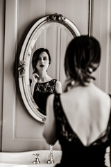portrait of beautiful young woman looking at herself in the wonderful mirror . Image in black and white color style © Masson