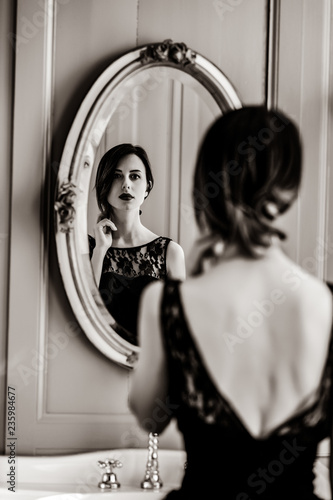portrait of beautiful young woman looking at herself in the wonderful mirror . Image in black and white color style - 235984677