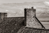 photo of old roof on one of buildings on the wonderful sky background . Image in black and white color style