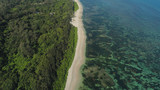 Aerial view of seashore with beach, lagoons and coral reefs. Philippines, Luzon. Ocean coastline with turquoise water. Tropical landscape in Asia.