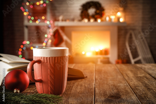 Leinwanddruck Bild wooden table with attributes of Christmas in the glow of the fireplace