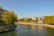 View from the Pont of Sully of the banks of the Seine River with people and autumn trees