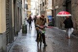 Italian man riding his bike through a cobble stoned village hold a red umbrella #4